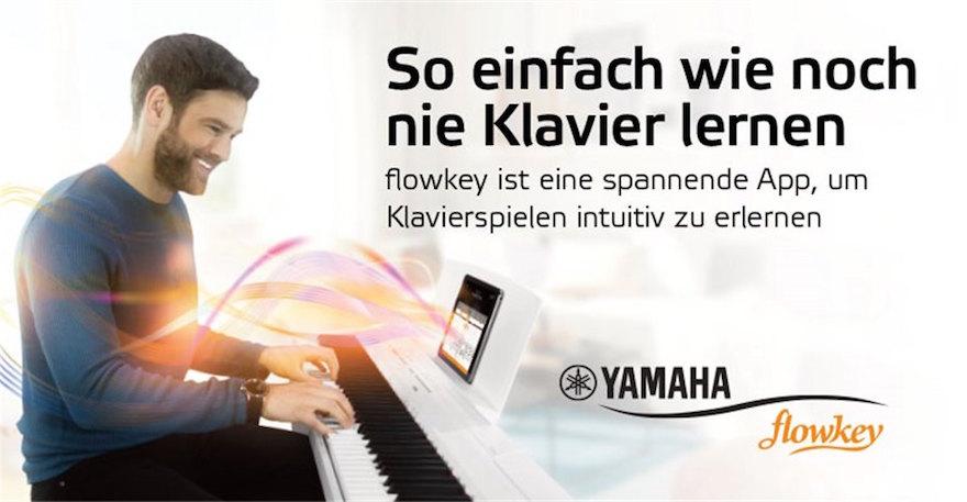 Mann am Klavier mit Tablet-PC mit Flowkey